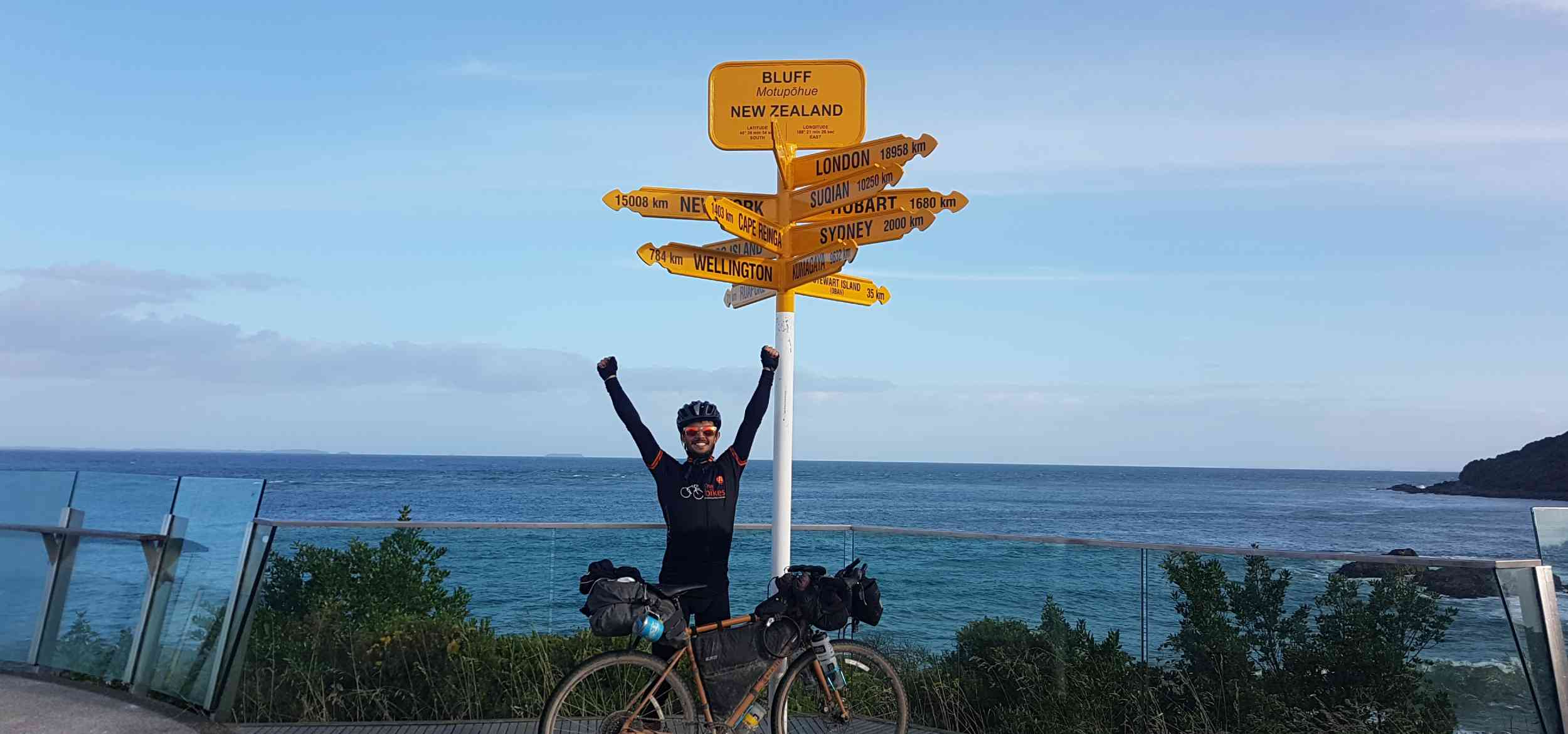 A cyclist standing next to his bike with bikepacking bags on it raising his arms in victory sign at Sterling Point
