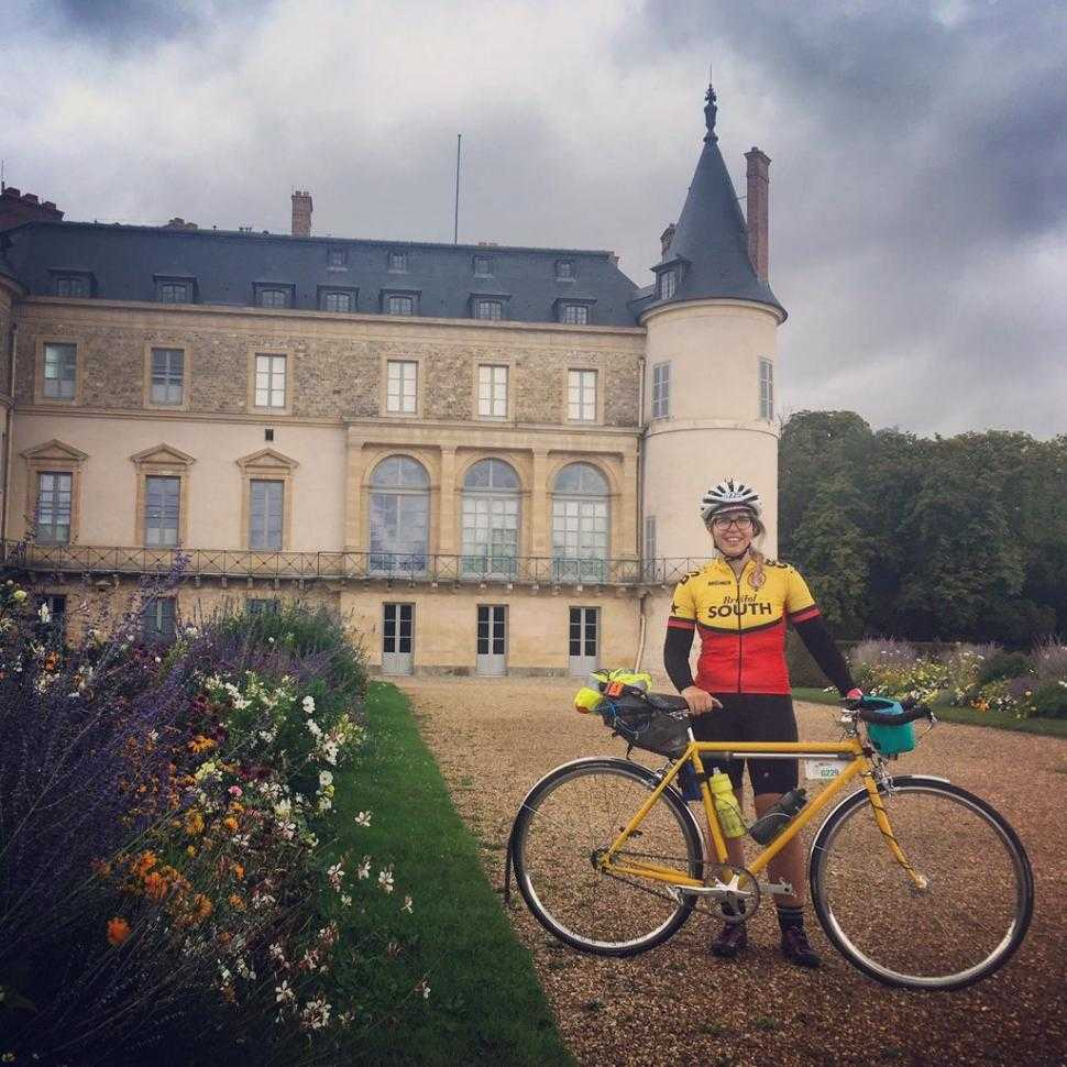 A woman standing next to her bike with a full bikepacking kit in front of a castle
