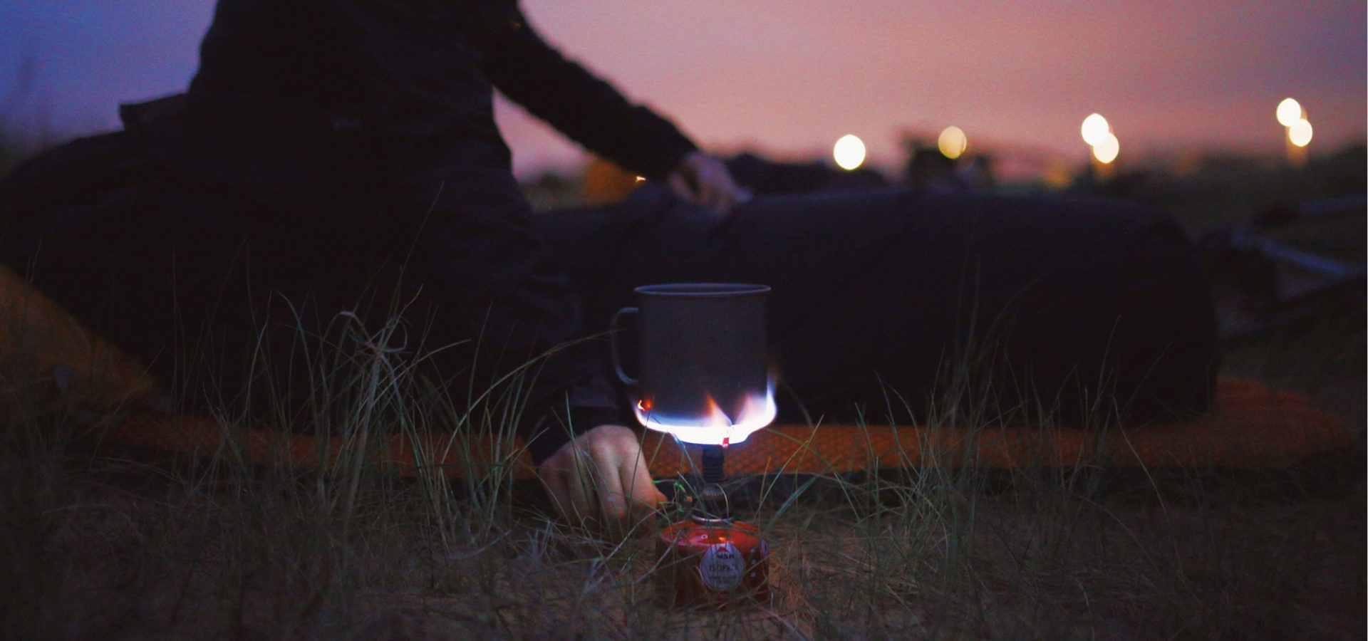 A person warming a cup on a gas cooker in the middle of the night