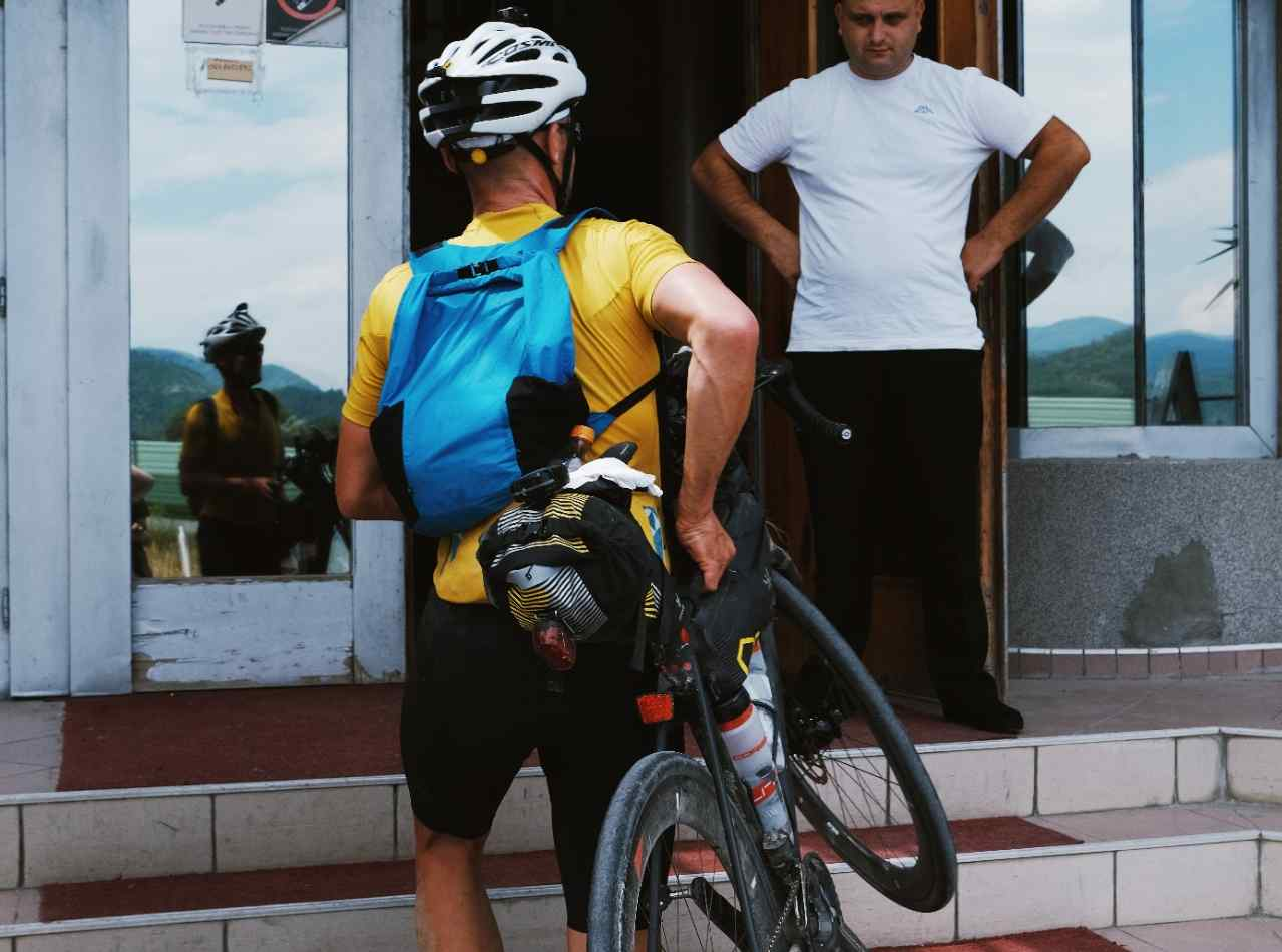 A man by back using a full bikepacking kit and a Packable Backpack carrying his bicycle through the stairs to a door