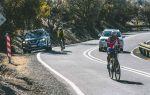 Two people riding a bike on a path across a mountain with two cars on it
