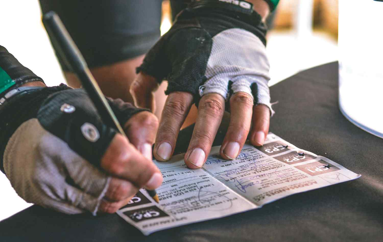 Close-up of two hands with bike mitt signing a paper