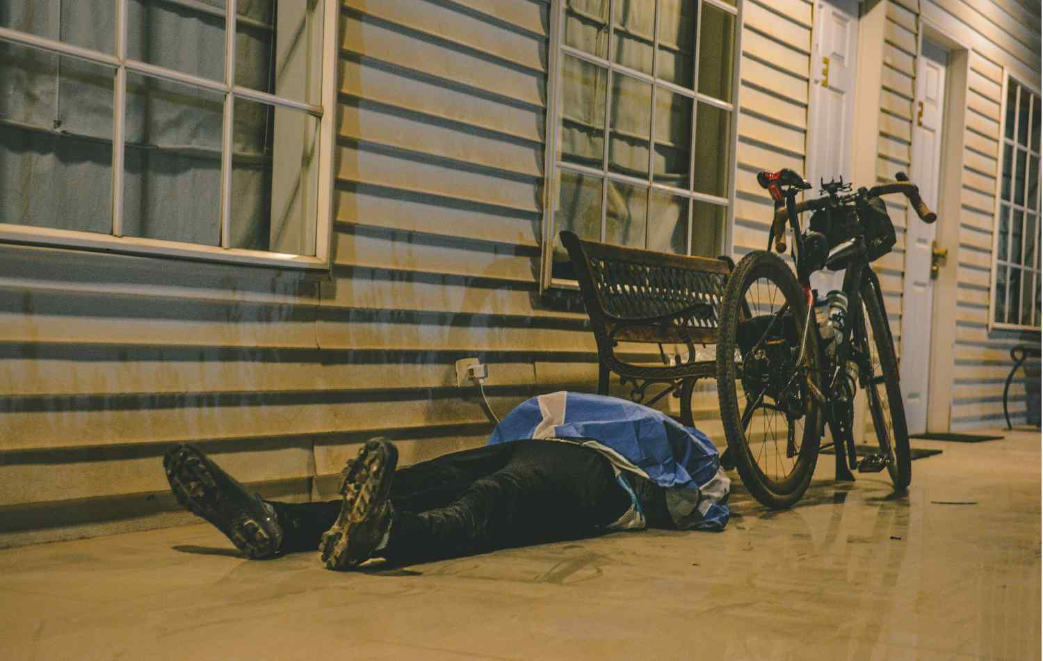 A person sleeping outside of a house on the floor next to his bike with bikepacking bags on it