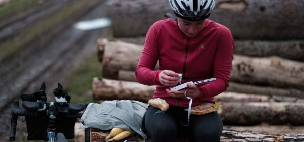 A woman sitting on a tree trunk next to her bike and a Packable preparing a sandwich