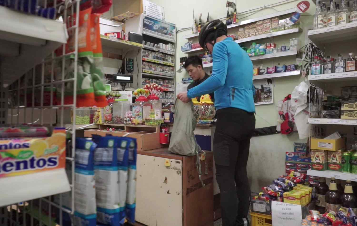 A man in a grocery store adding some product into his Packable Backpack