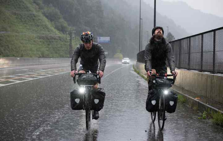 Two cyclists riding in pouring rain at The Japanese Odyssey