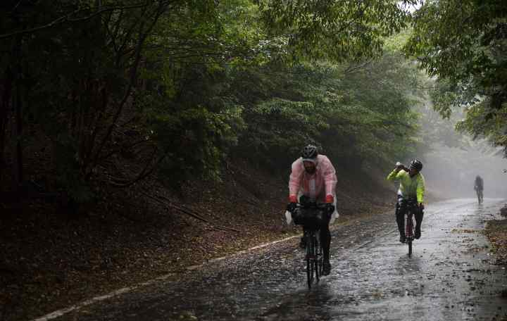 Cyclists riding a remote road in wet weather