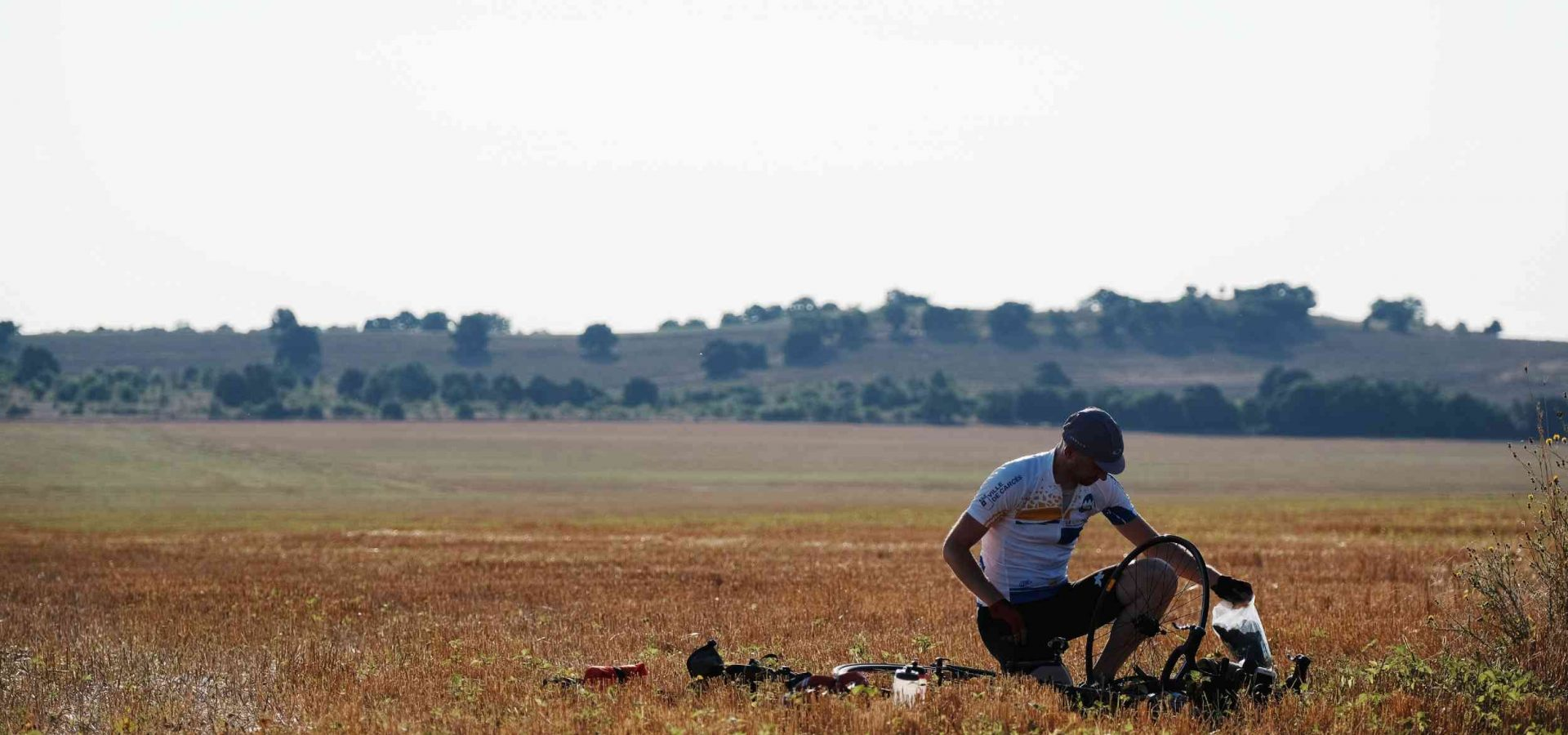 A cyclist sits in a field, repairing a puncture