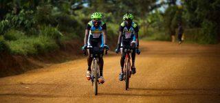 Two Rwandan riders on a dusty road during the Race Around Rwanda