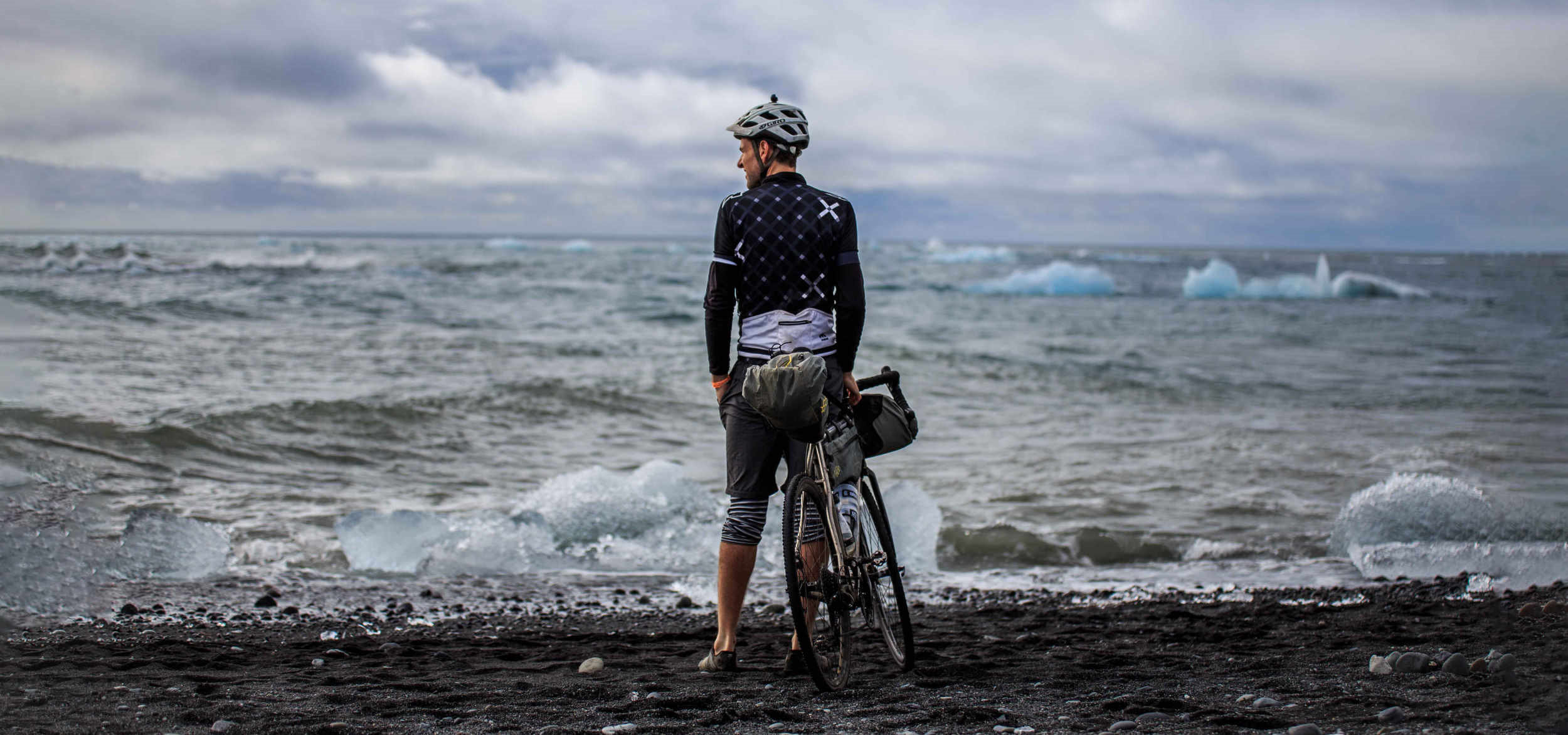 Man resting on bike during Bikepacking trip to Iceland's black beach with iceberg in the sea