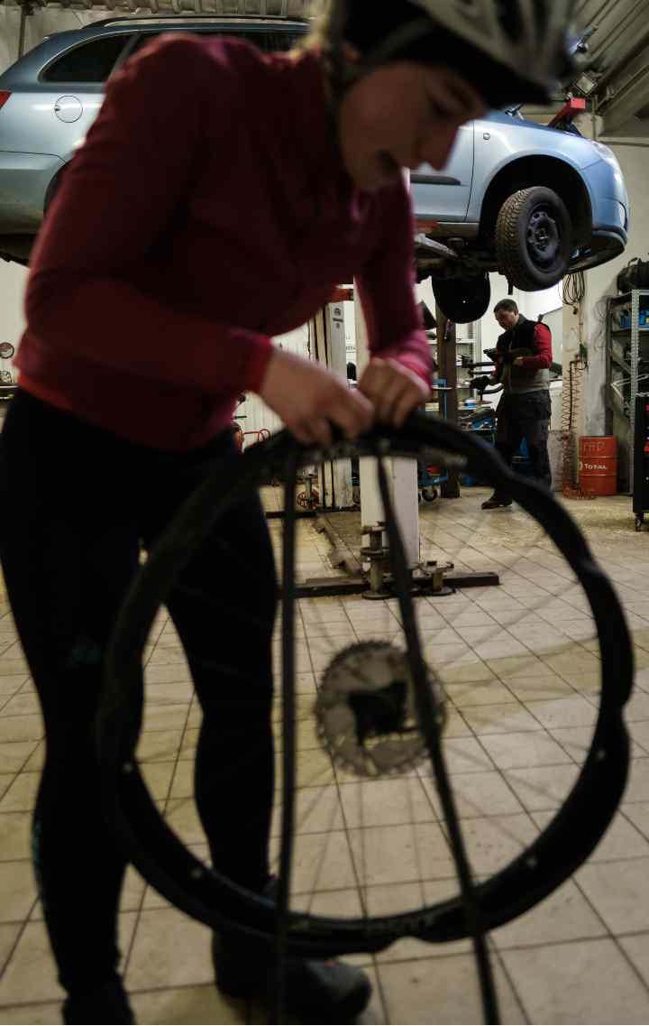 A cyclist removes a tyre from a wheel on the forecourt of a garage