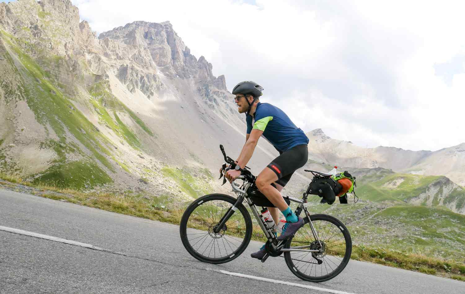 A man riding a bike with a full bikepacking kit through a hill in the mountain