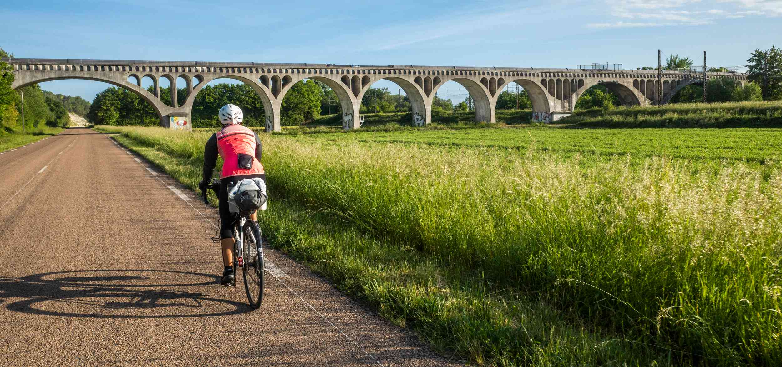 A cyclist heads toward a viaduct on a quiet road, with bikepacking bags on her bike and a camera over her shoulder