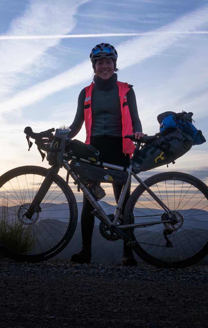 Meg Davies Standing standing next to her bike with a full Apidura bikepacking kit