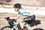 Georgina Panchaud riding her Bianchi in the desert with full bikpacking kit