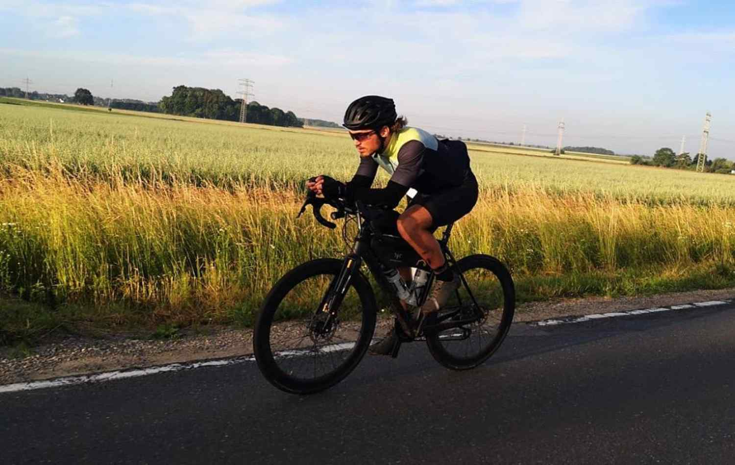 Rapha cycling alongside a cornfield on the aerobars with bikepacking luggage on his bike
