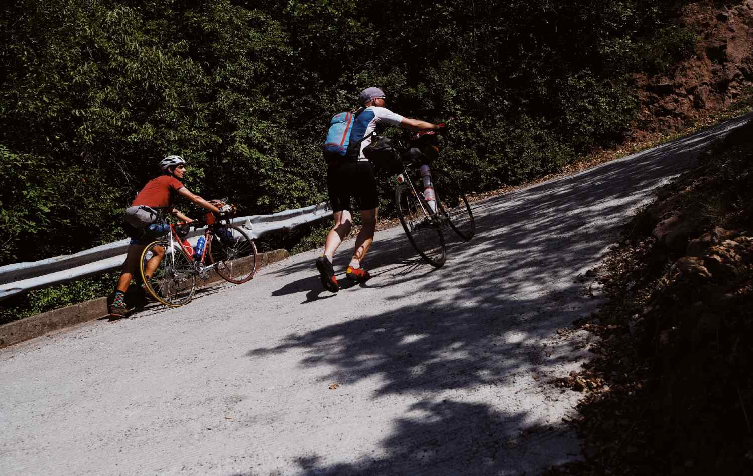 Two cyclists push heavily laden bikes up a steep road