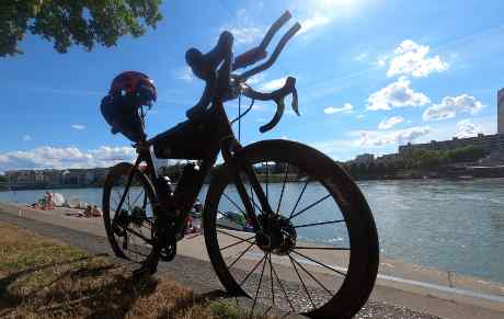 Ulrich's bike leans against a wall beside a lake in the afternoon sun