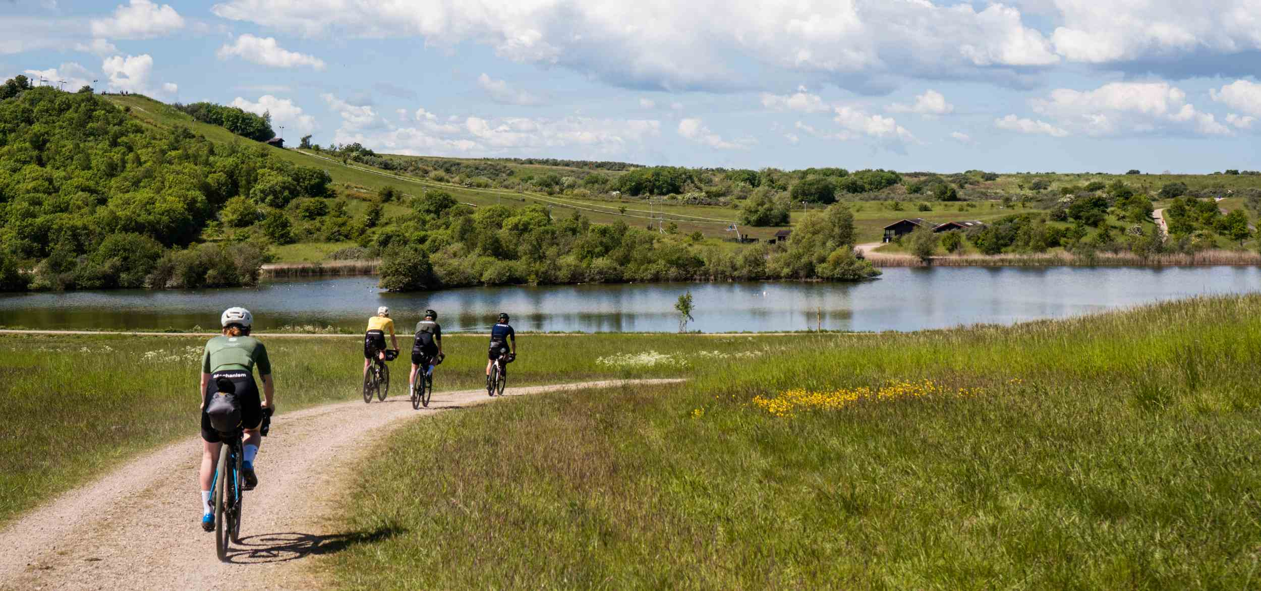 A line of cyclists ride alongside a lake on a gravel trail