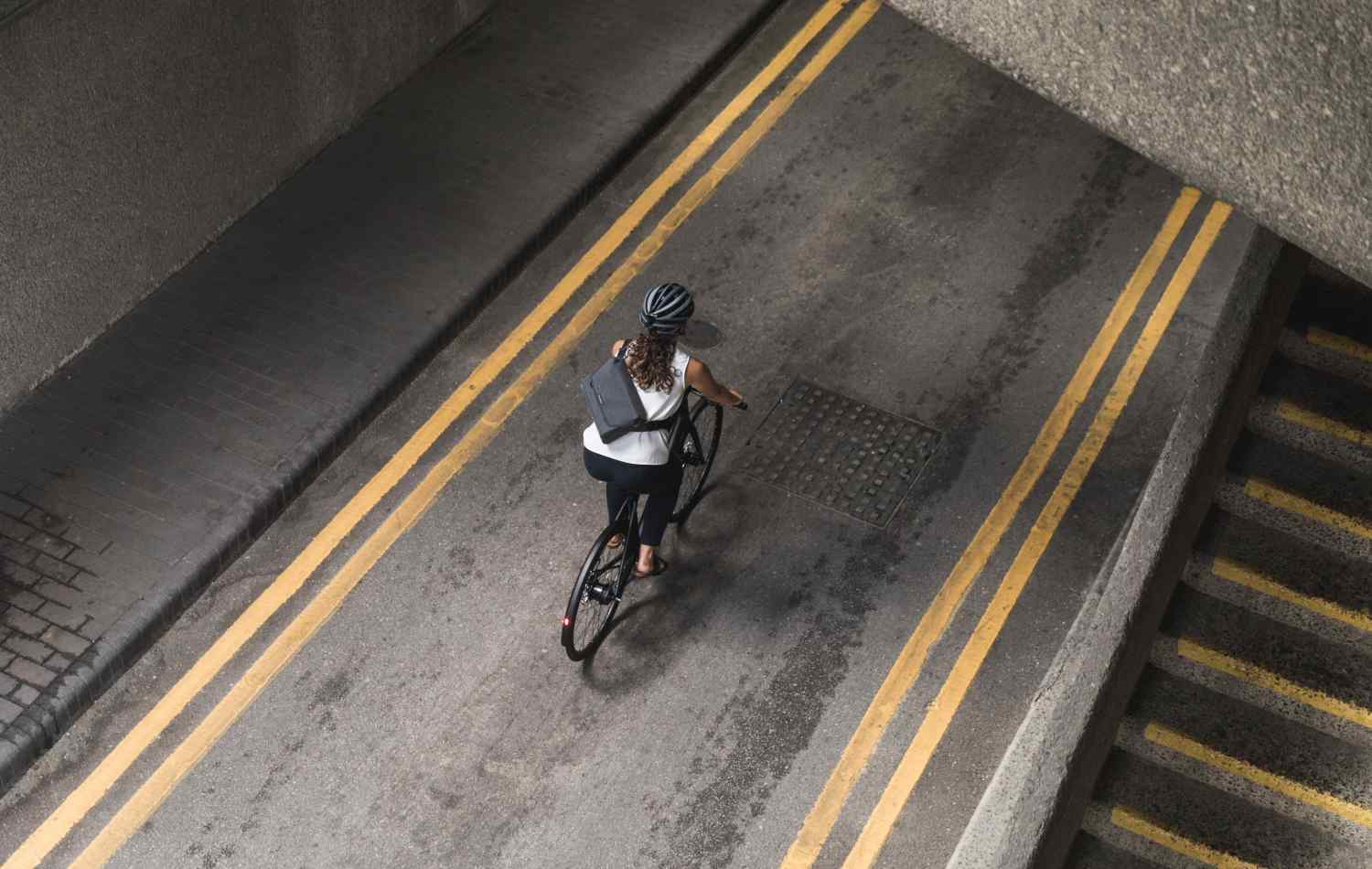 A woman cycles through the city with an Apidura City Messenger on her back