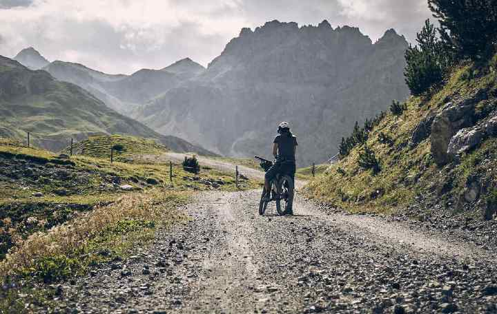 A cyclist on a mountain bike with backcountry bikepacking bags in front of mountains