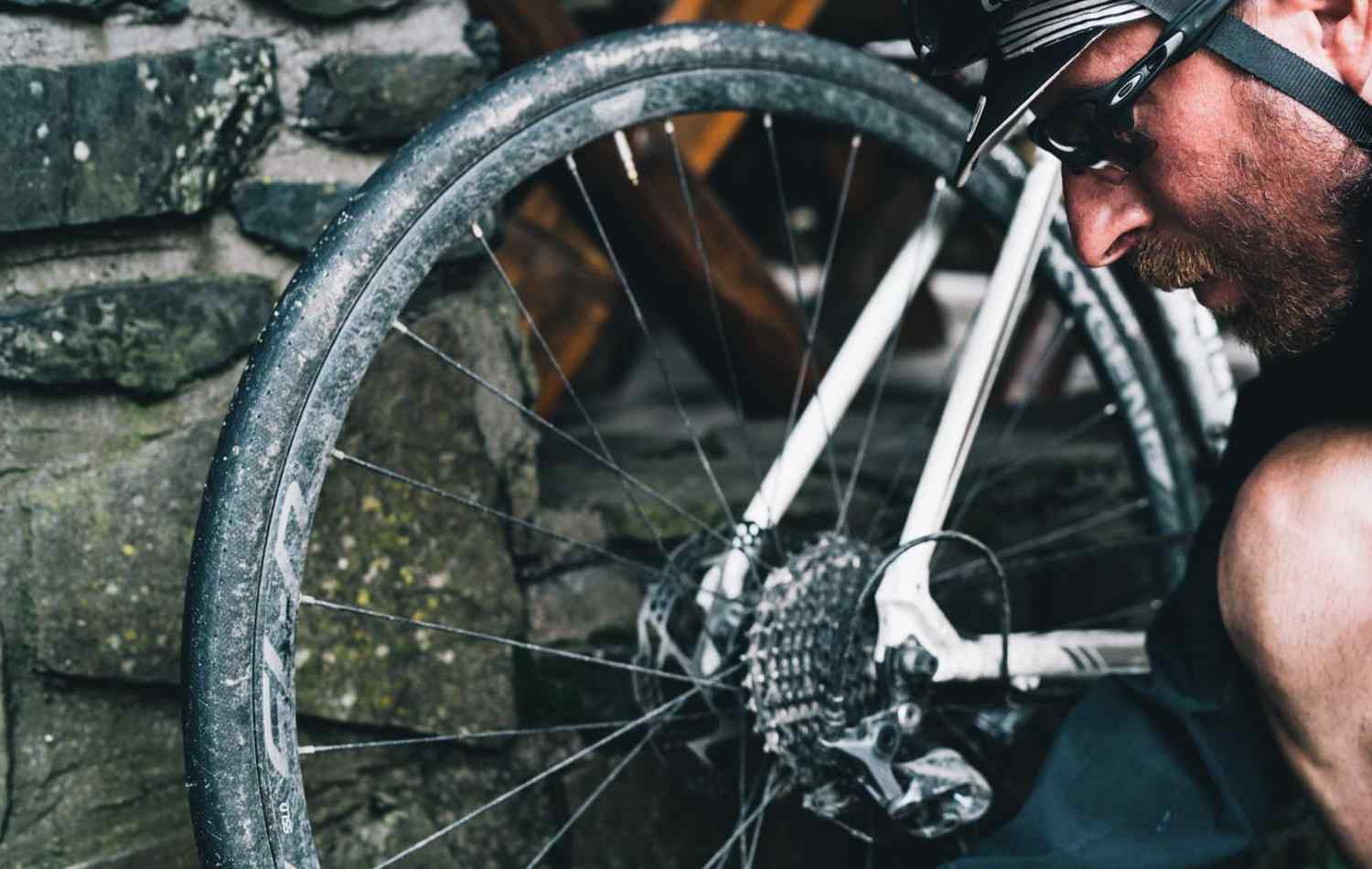 A wide road tire, covered in mud is inspected by the rider