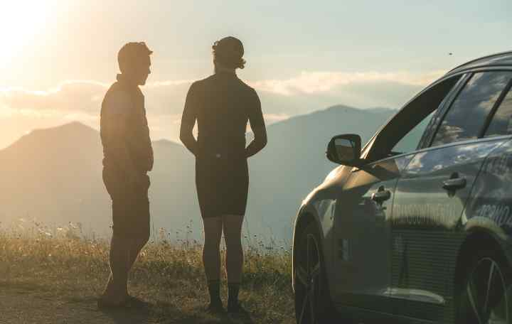 Mike Hall stands with a racer at sunset looking out over the mountains