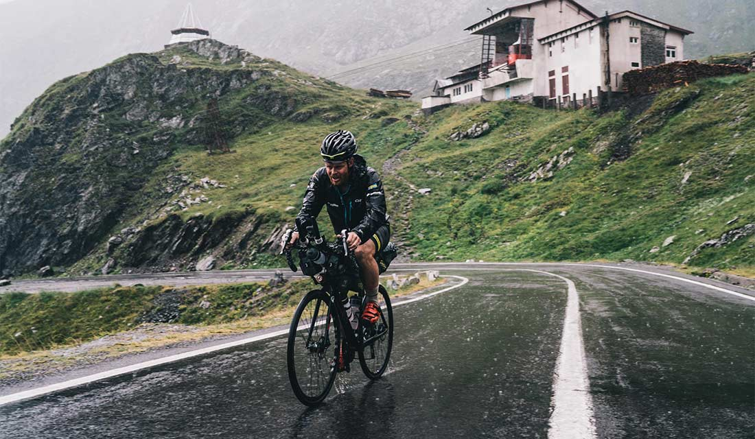 A rider on a mountain pass in the rain with Expedition series bags on their bike