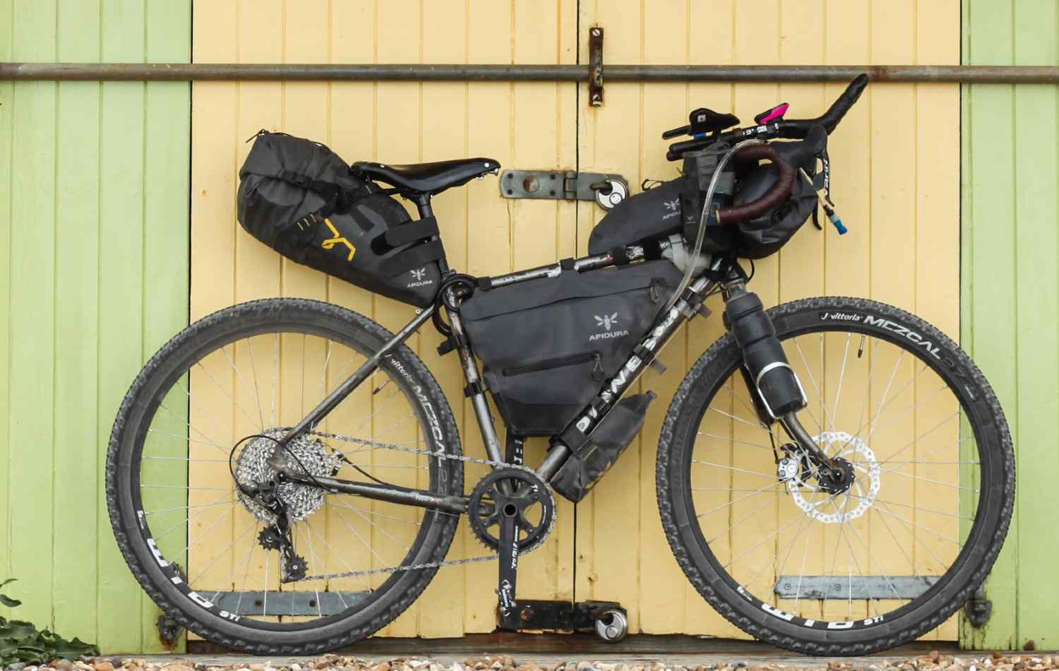 A bike leaning against a wall, covered in bikepacking bags