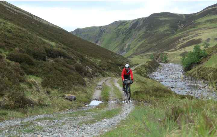 MArkus rides a gravel road on Glen Tilt with an Expedition Handlebar Pack on his bike