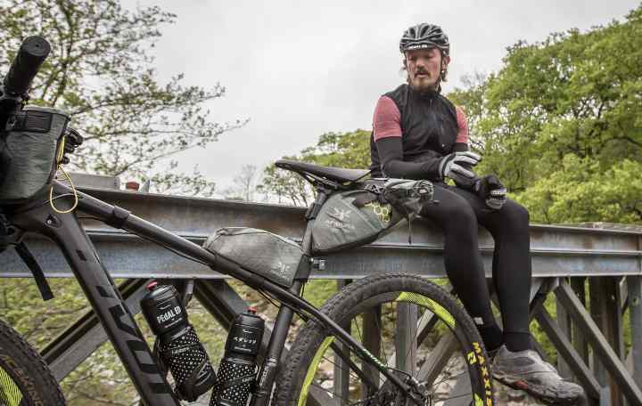 A cyclist sit next to his bike full of bikepacking bags