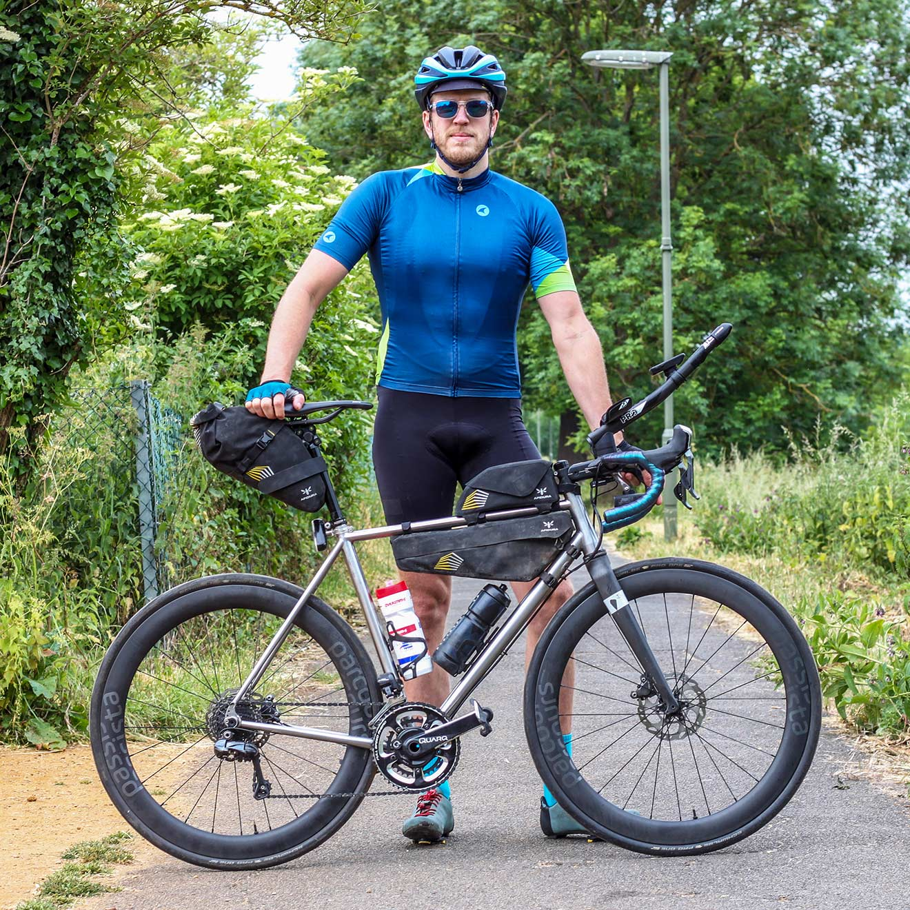 A cyclist standing next to his bike with a complete race kit: saddle bag, top tube bag, and frame bag