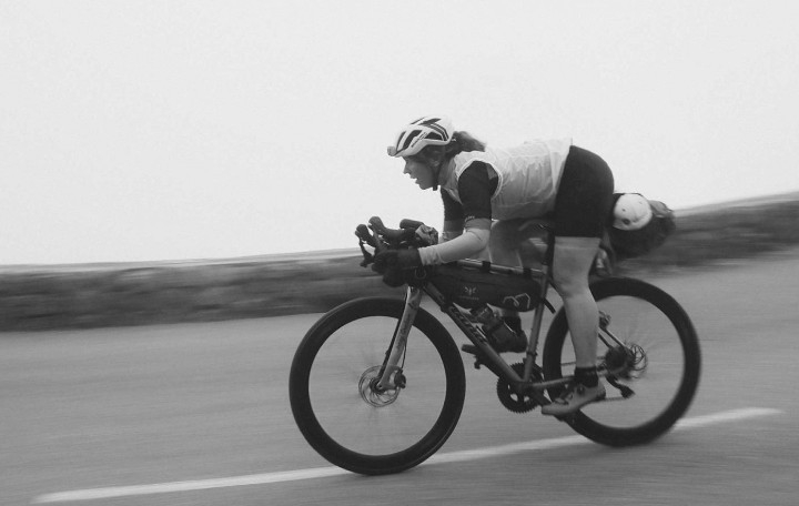 Jenny Graham riding on a misty road with Expedition packs on her bike