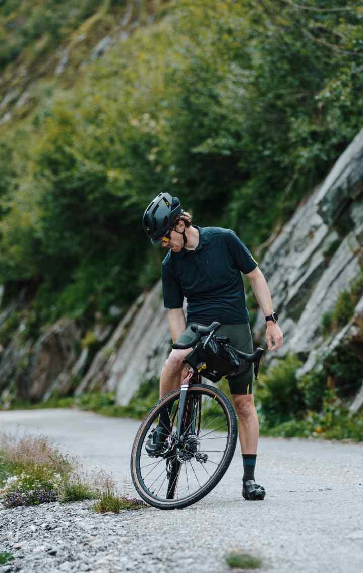 Seb checks his bike on a balcony road