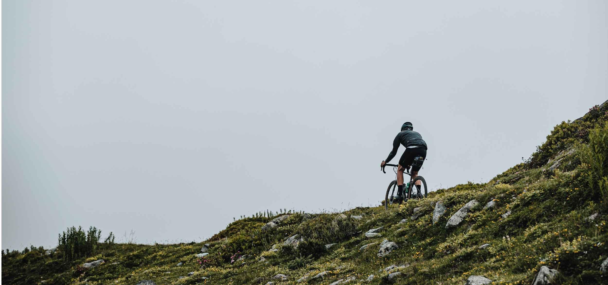 Seb rides along a ridge, backed by cloud
