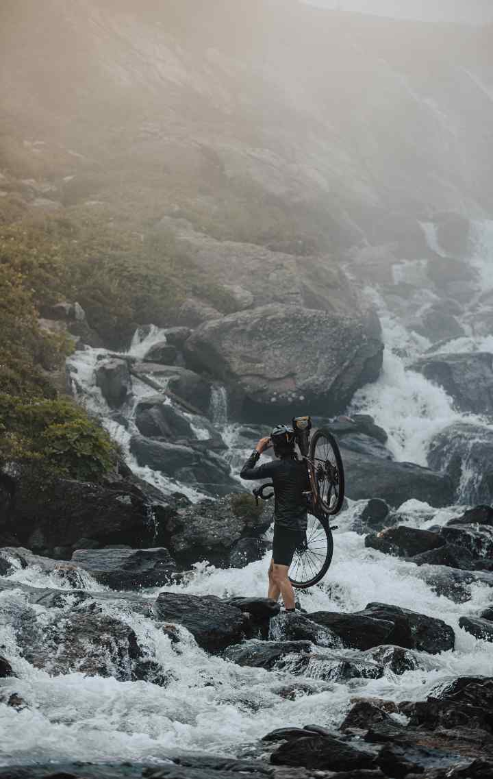Seb crosses an alpine waterfall, carrying his bike
