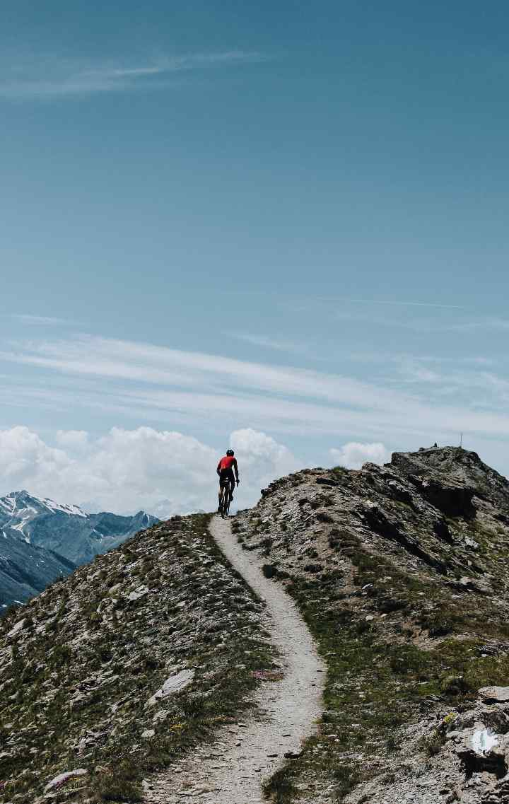 Seb rides a singletrack trail along the ridge of a mountain