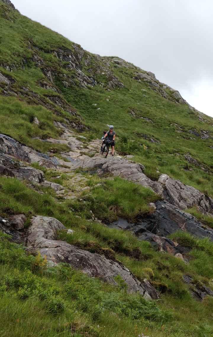 A cyclist climbs amongst rocks with her bike on a mountainside