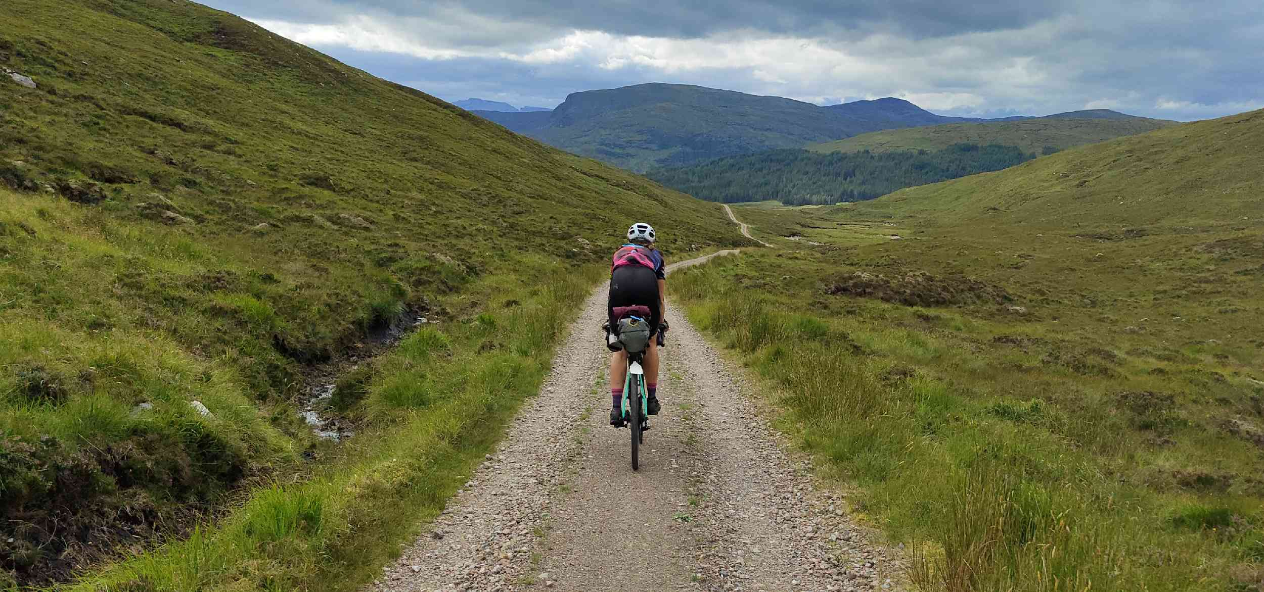 A cyclist rides away from the camera down a gravel trail