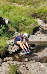 A cyclist sits at the side of a river, filtering water into her bottle