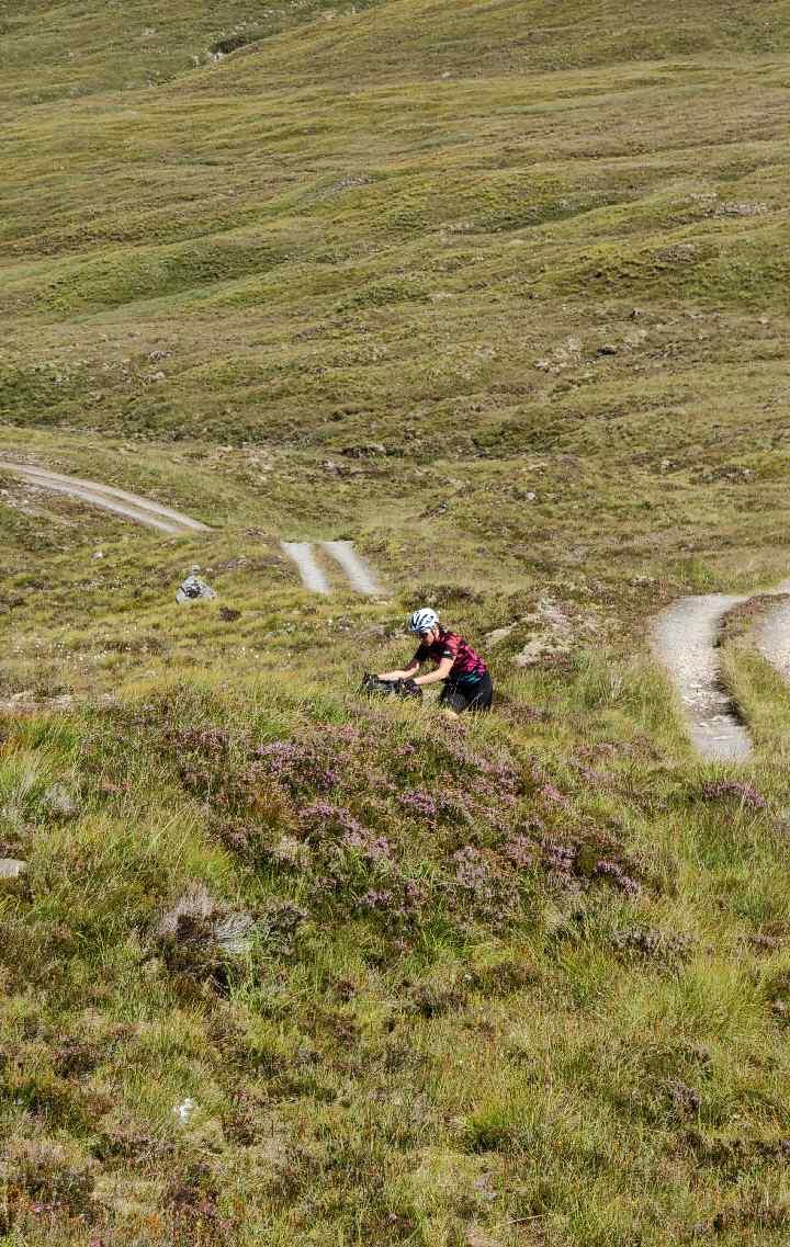 A cyclist wheels her bike up a steep climb on a gravel track through a grassy field