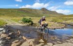 A cyclist rides across a ford in front of a mountain, her bike adorned with bikepacking bags