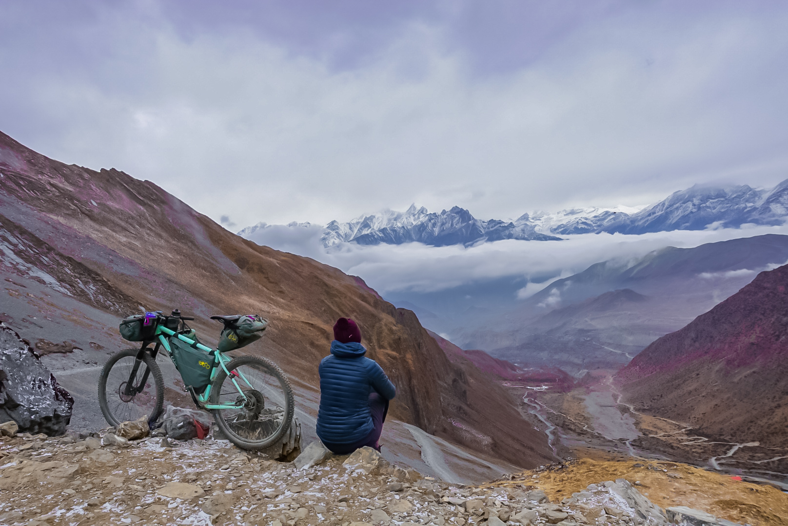 Jenny Tough sits on a Himalayan mountain taking in the view