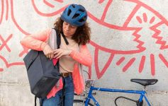 A cyclist reaches into the side pocket of the City Backpack
