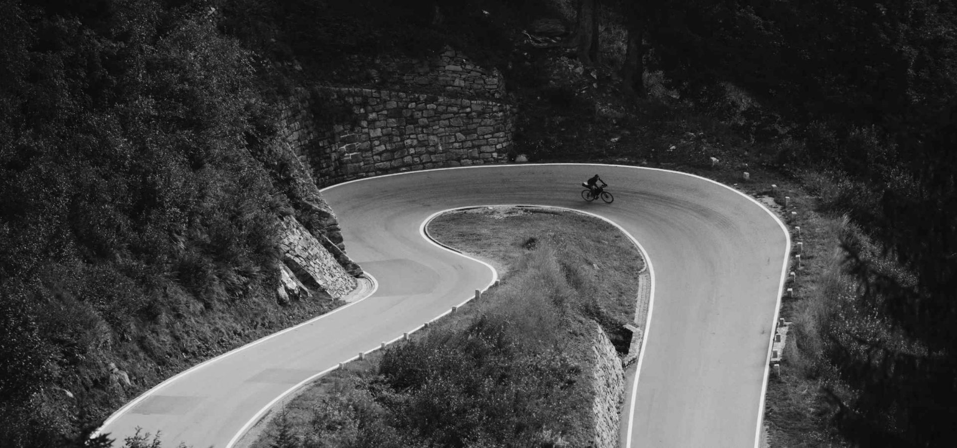 A cyclist racing around a hairpin