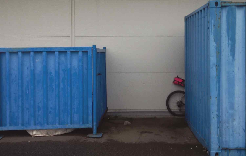 A bike partially hidden behind industrial bins