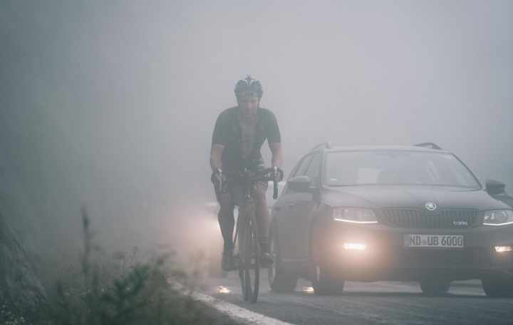 A rider on a busy road, shrouded in mist