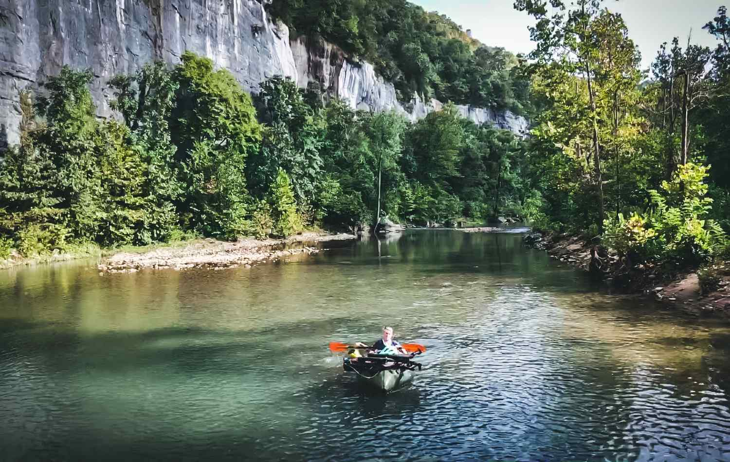 Scotti paddles along the river in her packraft, with her bike strapped onboard