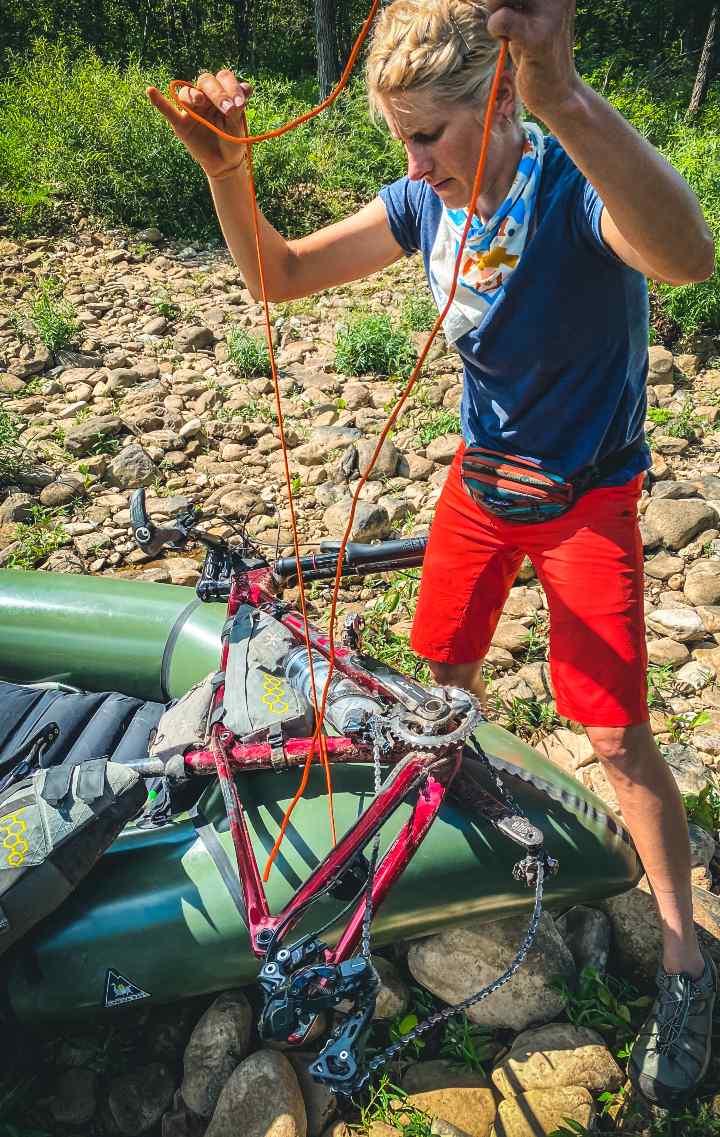 Scotti ties her bike to her packraft