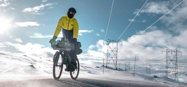 Pana riding his Trek mountain bike covered in Backcountry packs on a frozen road